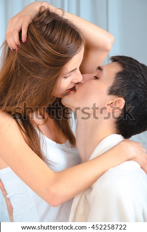 Vertical photo of young beautiful lovers kisses