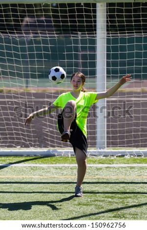 Vertical photo of young girl taking soccer ball off her knee with posts and net in background