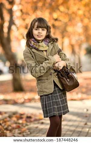 vertical photo,  stylish beautiful little gir lwalking in autumn park - stock photo