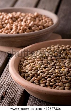Vertical photo. Two clay plates. Two earthen bowls with legumes. Plates with lentils and chickpeas. Detail of legumes. Plate on chopping board. Plates on old wooden board with worn grey surface. - stock photo