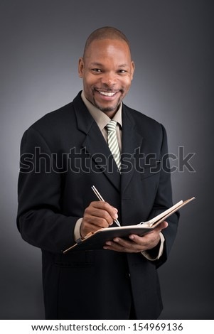 Vertical portrait of a black businessman making notes in his notebook over a grey background