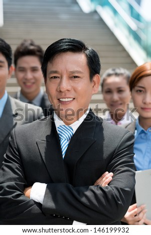 Vertical portrait of a business leader looking at camera on the foreground