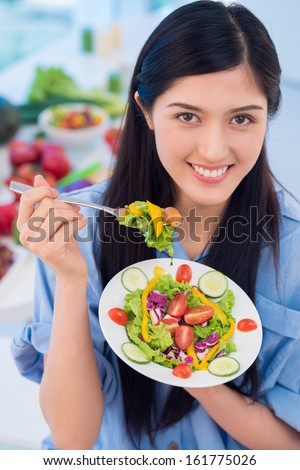 Vertical, portrait of a charming brunette showing a plate with freshly made salad - stock photo