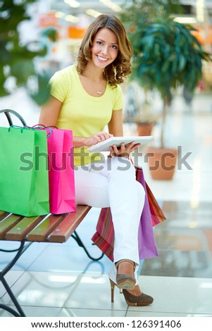 Vertical portrait of a charming girl sitting on a bench in a shopping gallery and using tablet - stock photo
