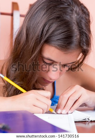 Vertical portrait of a latin teen working on her school project or writing a letter