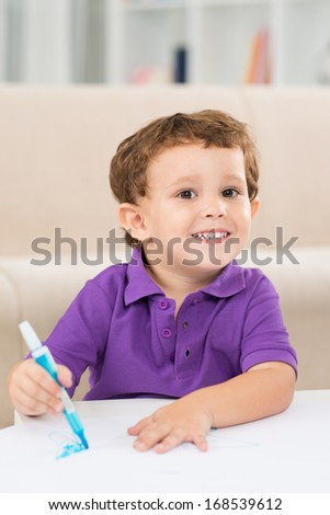 Vertical portrait of a little cheerful boy smiling and looking at camera while painting at home  - stock photo