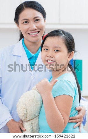 Vertical portrait of a little girl showing �¢??ok�¢?� sign after doctor's examination on the foreground - stock photo