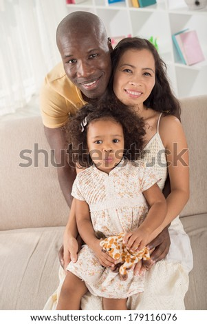 Vertical portrait of a mixed adorable family at home  - stock photo