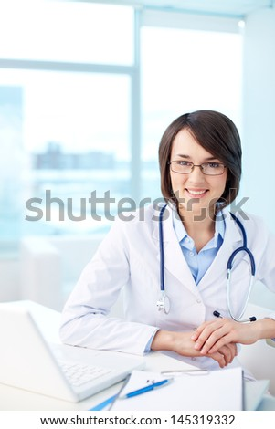 Vertical portrait of a modern medical worker with a charming smile - stock photo