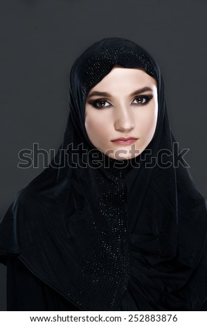 Vertical portrait of a Muslim woman in traditional clothes on gray - stock photo