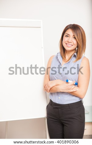 Vertical portrait of a pretty business woman standing next to a flip chart and ready to give a presentation - stock photo
