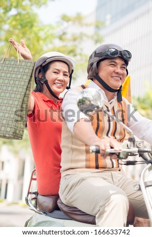 Vertical portrait of a senior woman with a shopping bag posing at camera while her husband riding a scooter on the foreground  - stock photo