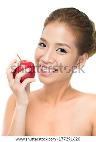 Vertical portrait of a smiling beauty with a juicy apple against a white background  - stock photo