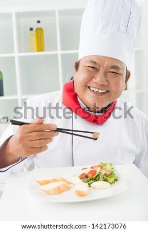 Vertical portrait of a smiling cook tasting his dish - stock photo