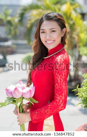 Vertical portrait of a young lady with lotus in hands