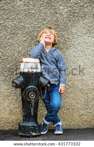 Vertical portrait of adorable little boy of 4-5 years old, having fun outdoors, playing with black hydrant - stock photo