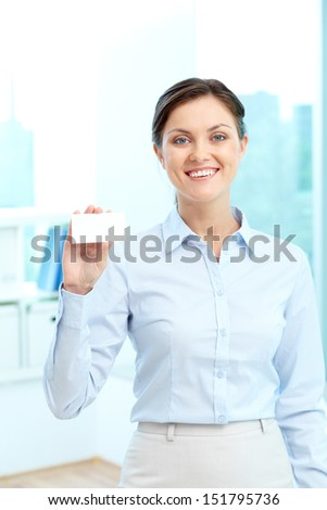 Vertical portrait of an attractive office girl holding a blank visiting card