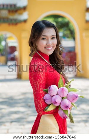 Vertical portrait of an attractive woman in traditional wearing with lotus in hands