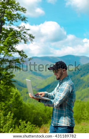 Vertical portrait of cheerful young man working on laptop in the mountains and smiling - stock photo