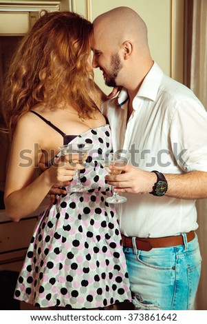 Vertical portrait of flirting beautiful couple at party. Celebrate, disco, party, nightlife, entertainment, friendship concept. - stock photo
