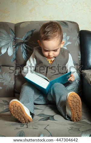 vertical portrait of little boy in elegance suit reading a book sitting on couch