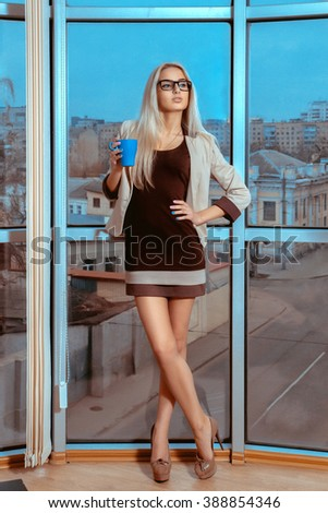 Vertical portrait of sexy blonde woman with cup of tea by the large window with city views. City views behind the window in the office. Business woman drinks tea. Business concept. - stock photo