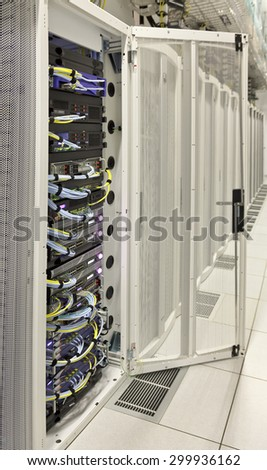 vertical rack of telecom and server equipment with opened cabinet's door in computer data centre - stock photo