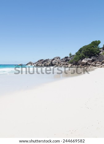 Vertical seascape with beautiful turquoise waves of the transparent sea water with white foam breaking on the sea shore with fine sand beach in the Seychelles and clear sky - stock photo