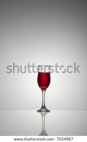 Vertical shot of a backlit wine glass over off-white background. The glass is half filled with red wine