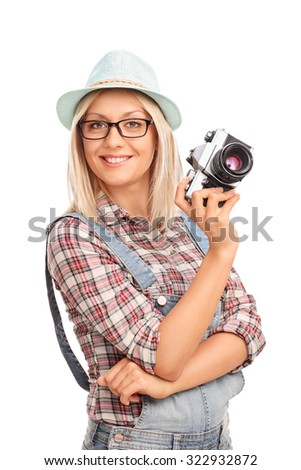 Vertical shot of a beautiful female photographer with blue cap holding a camera and smiling isolated on white background - stock photo
