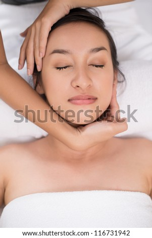 Vertical shot of a beautiful young woman enjoying spa treatment - stock photo
