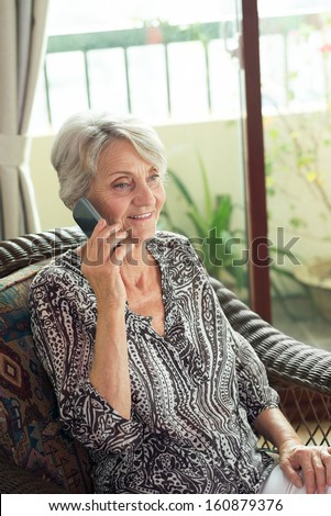 Vertical shot of a charming retiree making a call - stock photo