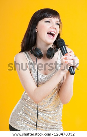 Vertical shot of a charming young woman singing with a microphone - stock photo