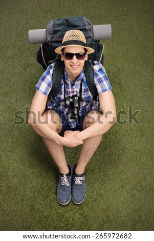Vertical shot of a cheerful young hiker sitting on grass, carrying a backpack with hiking equipment and looking at the camera  - stock photo