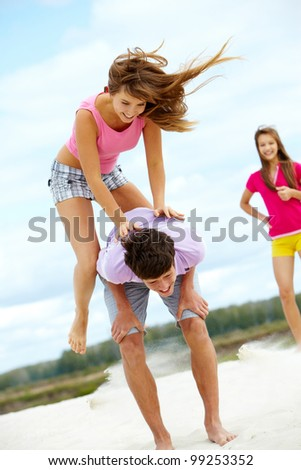 Vertical shot of a girl jumping over her friend�¢??s back, vivid an dynamic photo - stock photo