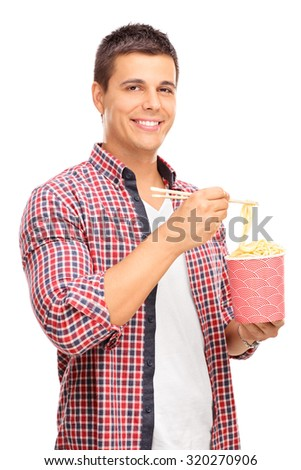 Vertical shot of a joyful young man eating Chinese noodles with sticks and looking at the camera isolated on white background - stock photo