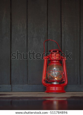 vertical shot of a red old lantern on the dark wet wooden floor with reflection on the floor