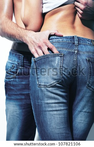 Vertical shot of a seductive couple wearing jeans which accentuate beautiful form - stock photo