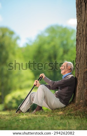 Vertical shot of a senior gentleman sitting in park by a tree and holding a cane on a beautiful summer day - stock photo