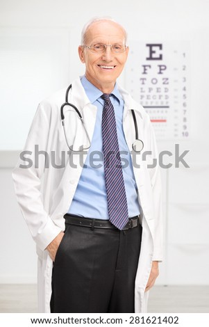 Vertical shot of a senior optician in a white coat posing in his office in front of an eyesight test and smiling - stock photo