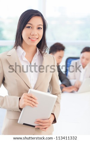Vertical shot of a smiling smartly dressed business girl holding a digital pad