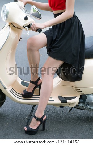 Vertical shot of a stylish young beauty sitting on a scooter - stock photo