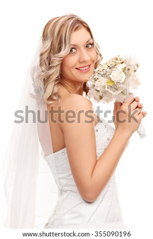 Vertical shot of a young bride in a white wedding dress holding a bouquet of wedding flowers and looking at the camera isolated on white background - stock photo