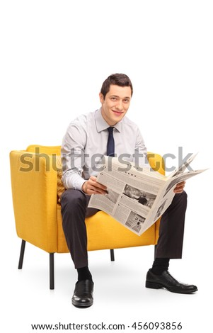 Vertical shot of a young businessman reading a newspaper seated on a yellow armchair isolated on white background - stock photo