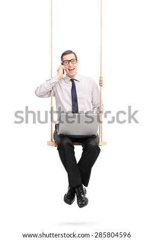 Vertical shot of a young businessman speaking on his cell phone seated on a swing isolated on white background - stock photo