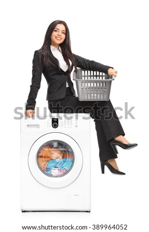 Vertical shot of a young businesswoman waiting for the laundry seated on a washing machine isolated on white background - stock photo