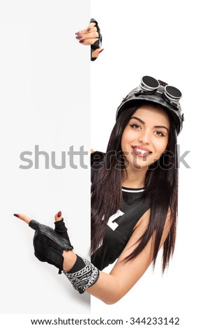 Vertical shot of a young female biker pointing on a blank signboard with her finger isolated on white background - stock photo