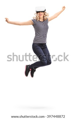 Vertical shot of a young joyful woman experiencing virtual reality and jumping shot in mid-air isolated on white background - stock photo
