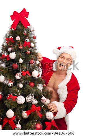 Vertical shot of a young man in a Santa costume with unbuttoned shirt posing behind a Christmas tree isolated on white background - stock photo