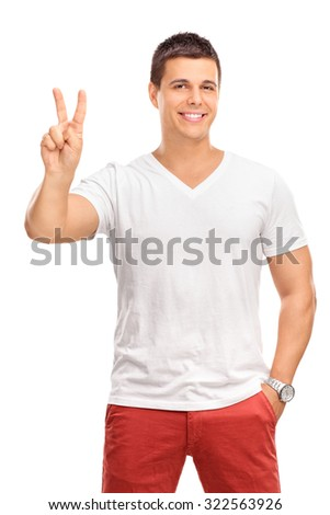 Vertical shot of a young man making a peace hand gesture and looking at the camera isolated on white background - stock photo